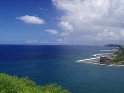 濃紺の海に青い空とやわらかな緑の山並み