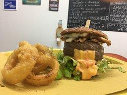 JucyLucy, hamburger da 200gr di bovino di Arborea con cuore di cheddar, lattuga, pomodoro, guanciale di Belvì e salsa BBQ con side di anelli di cipolla freschi.