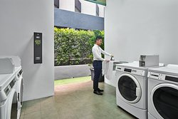 Self-service launderette offering washers, dryers, irons and ironing boards located on Level 4.