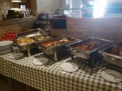 buffet consisting of potatoes, lampuki local fish, chicken and meat