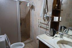 Taken near the bathroom door to show the shower stall & bathroom vanity & sink.