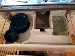 Kitchen with plates and cutlery, but in an obviously chipped cabinet