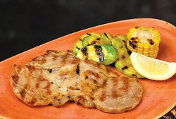 Grilled Pork neck chop served with grilled courgettes and corn