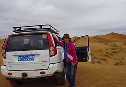 Lady Tourist standing beside her 4 wheel drive