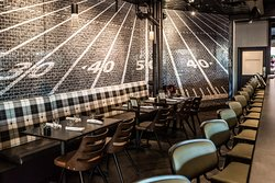Bar and table seating with custom football-inspired mural