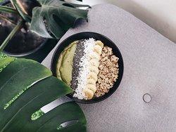 Matcha Green Smoothie Bowl  Banana blend w avocado, baby spinach, matcha powder, almond milk, topped w granola, banana, coconut flakes and chia seed.