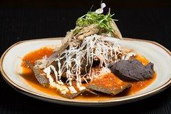 Chilaquiles, totopos de tortilla azul, con crema acida vegana, queso de aceite de coco, cebolla morada, se pueden servir con setas y salsa a escoger, roja, verde, o guajillo.
