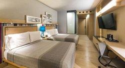 Habitación Privilege con dos camas y TV de 55 pulgadas.