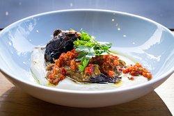 Roasted eggplant is placed on a Jerusalem tahini and tomato salsa