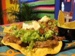 KUKULKAN: 3 tostadas de maíz con frijoles refritos, cochinita pibil, lechuga, pico de gallo, jalapeños curtidos. Acompañado con crema agria, totopos y guacamole.