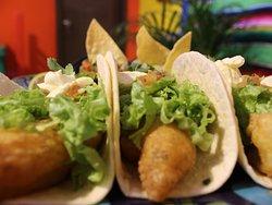BAJA FISH TACOS: 3 tacos de pescado capeado con tortilla de trigo al estilo Baja California Sur, con lechuga. Acompañados con totopos, pico de gallo, crema agria y guacamole.