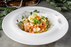 Russian salad with weak salt salmon and red caviar