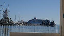 Blick auf Leuchtturm und Kreuzfahrtschiff über den Hafen hinweg