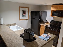 Kitchen with full sized refrigerator, oven, and microwave.  Utensils and dishes in cupboard.
