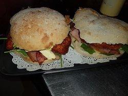 Chicken Schniztel Bennys - chicken schnitzel, baby spinach, bacon, cheese & hollandaise sauce on a Turkish roll, toasted!