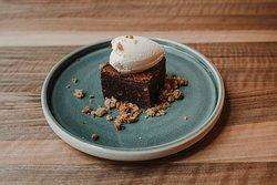 Brownie casero con salsa de chocolate, acompañado de helado al gusto.