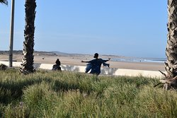 A woman is dancing on the beach boardwalk while her friend is drumming.
