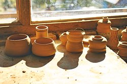 Some freshly made clay pots drying in the natural sunlight.
