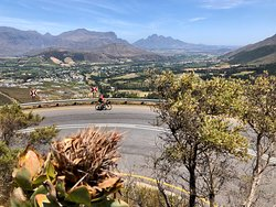 Road Cycling up Franschhoek Pass in the Cape Winelands, with a view of Franschhoek and the Drakenstein Valley in the background.