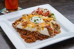Roasted Pork & Green Chili Enchiladas  House-roasted pork, pork green chili and cheese inside flour tortillas. Topped with queso, green chili, sour cream and cilantro. Served on a bed of rice and beans. Pico de gallo and lettuce on the side