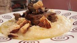 polenta morbida con costine di maiale disossate e cotte alla plancia, carciofi croccanti e granella di parmigiano soffiato.