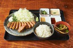 """【牛かつ もと村】は、『牛かつを日本の食文化にする』という想いを胸に""""牛かつ""""の美味しさを実直に提供して参ります。 ミディアムレアに揚げた牛かつを石盤で炙り、わさび醤油"""" でお召し上がりください。 厳選したパン粉を細かく挽き、薄い衣をまとわせ揚げるのでさっぱりしております。 特製の山わさびソースや岩塩で食すと牛かつの美味しさが更に引き立ちます。"""