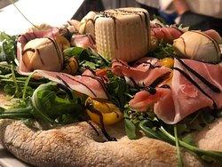 """La mitica pizza """"Il figlioccio"""" con rucola, pomodorini gialli, speck, aceto balsamico, mozzarella di bufala affumicata (dopo cottura), burrata all'uscita, olio e.v.o."""