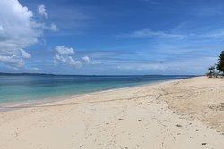 Patrick on the beach view is the beautiful Island of Daku