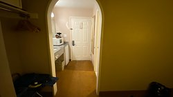 View of the entry door with the wash basin, microwave, fridge and coffee maker on the left