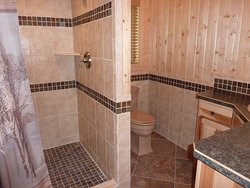 Huge custom ceramic tile shower with double shower head in the one bedroom, lakefront Point Vacation Home Cabin.