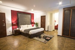 Our executive room with a king size bed, en-suite bathroom, a mini fridge, TV and 2 sofa beds.