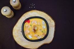 Cremosa sopa de coco, chontaduro y tubérculos de la región con mariscos salteados.