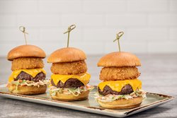 ALL-AMERICAN SLIDERS - Three mini-burgers with melted American cheese, crispy onion ring and creamy coleslaw on a toasted brioche bun.