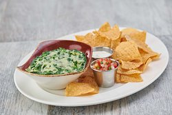 SPINACH & ARTICHOKE DIP - A creamy blend of romano and cheddar cheese, chopped spinach and artichoke hearts, served with crispy tortilla chips and house-made pico de gallo on the side.