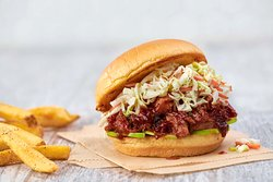BBQ PULLED PORK SANDWICH - Hand-pulled smoked pork with our house-made barbecue sauce, served on a toasted fresh bun with coleslaw and sliced Granny Smith apples.