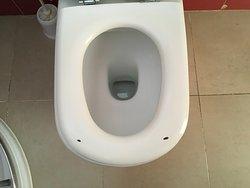 """Abgesplitterter, wackliger Toillettendeckel und daneben eine mindestens 2 Jahre alte """"Igitt"""" Toilettenbürste."""