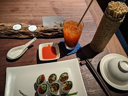 Summer roll and fruit drink with reed straw.