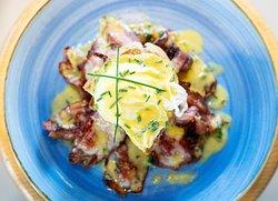 Brunch: uova alla Benedict con bacon, salsa olandese ed erba cipollina.