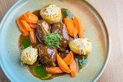 Geschmorte Schweinsbackerl in Honig-Malzbiersoße, Krenerdäpfel und Karottengemüse