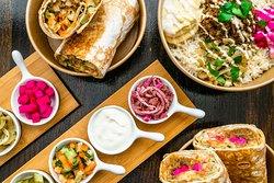 Overhead: Baharat Spiced Chicken Saj Wrap, Beef + Taheen Bowl, Beef + Taheen Saj Wrap