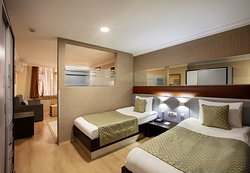 With two single beds and a sofa, Twin Bed Suites can accommodate 3 people and offer an economical solution for friends traveling together.  A semi-transparent glass wall separates the bedroom from the living room with sofa and an open kitchen.