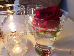 Centerpiece decor: rose floating in water, oil lamp.