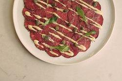 Carpaccio de res - Hojas de filete de cabrería, aioli de chiltepin, arugula y pimienta.