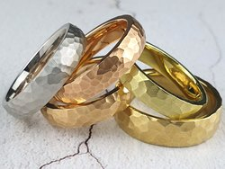 Men's wedding rings in platinum and various shades of 18ct gold, all with a hammered finish.