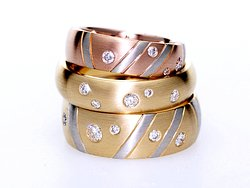Three custom-made wedding rings in 18ct gold with scattered diamonds.