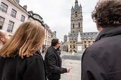 Ben from 'Ben's Ghent - Free & Private Tours' on Saint Bavo's square, pointing at Saint Bavo's Cathedral. Inside the cathedral the world famous triptych 'The Adoration of the Mystic Lamb' aka 'The Ghent Altarpiece' by Jan van Eyck. Ben is guiding his free exclusive Highlights of Ghent Tour here. This is one of 3 EXCLUSIVE FREE TOURS: 1. The free tip based Highlights of Ghent Tour 2. Free tip based Gorgeous Ghent by night Tour 3. Free Graffiti & Street Art Tour Join a FREE TOUR now!