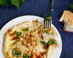Hummus Pureed chickpeas with tahini, seasoned with cumin, winegar, garlic white pepper, oil and lemon juice