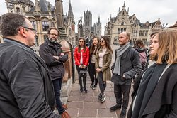 Tour guide Ben from Ben's Ghent on top of Saint Michael's Bridge, telling stories about the old medieval harbour, Saint Michael fighting the dragon, Saint Michael's church and the iconic three towers of Gent: Saint Nicolas Church, the Belfry aka the watch tower and Saint Bovo's Cathedral. A small group of young people is surrounding Ben.