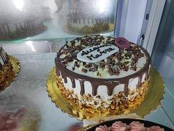 torta composta con pandispagna , crema chantilly aromatizzata , inserto di frutta decorazione di frutta e granelle