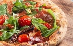 Pomodori pelati, mozzarella especial, tomate seco, sob cama de rúcula, presunto de Parma italiano, grana padano e orégano.